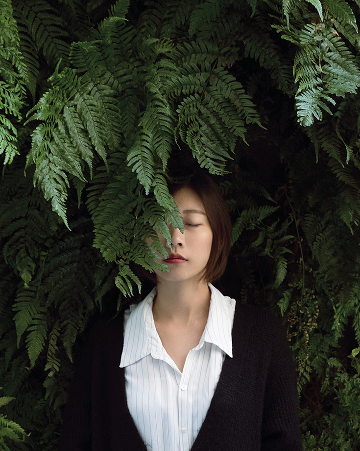 A woman wearing a white shirt under a black cardigan. Half her face is covered with a leaf.