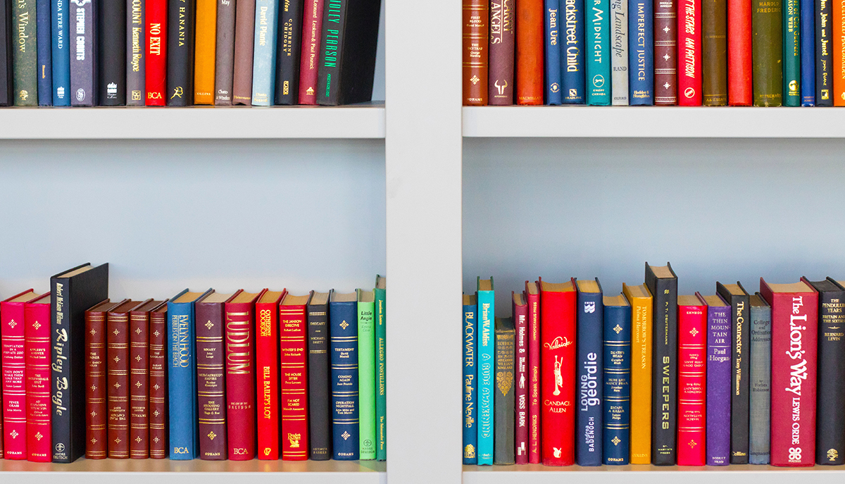 A photo of a bookshelf with various different sizes and colours of books.