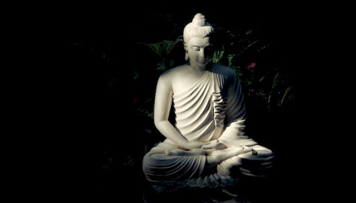 Buddha statue in shadows.