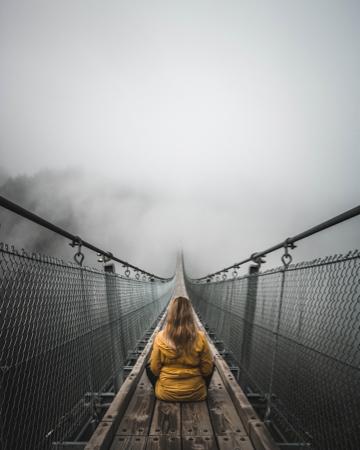 Woman meditating on footbridge in the fod.