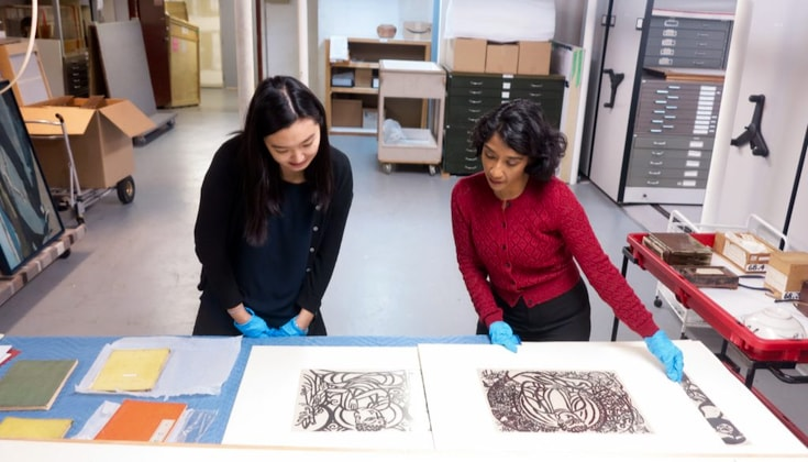 Two women look at art prints in a gallery lab.