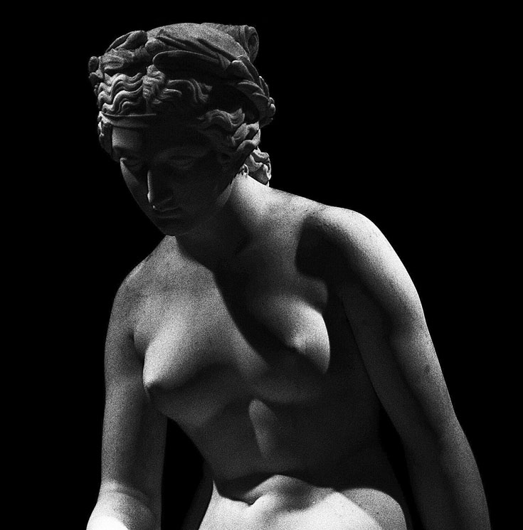 A black and white photo of a marble sculpture of a naked woman from the waist up.