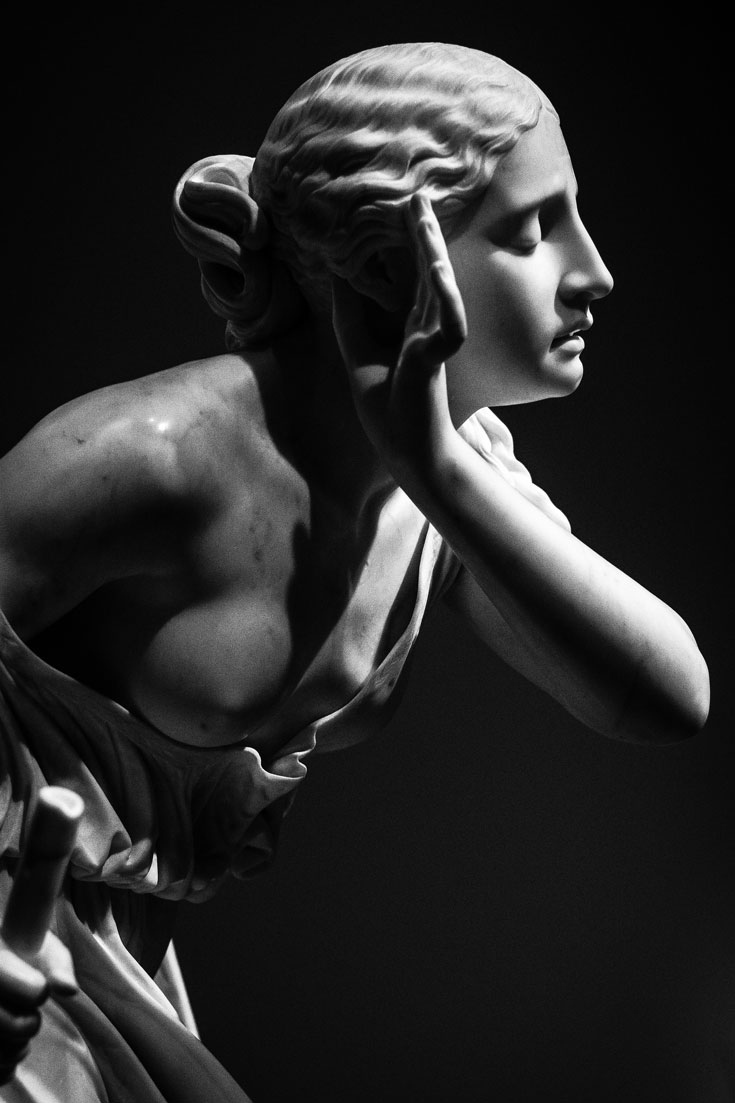 A black and white photo of a marble statue of a woman holding her hand to her ear.