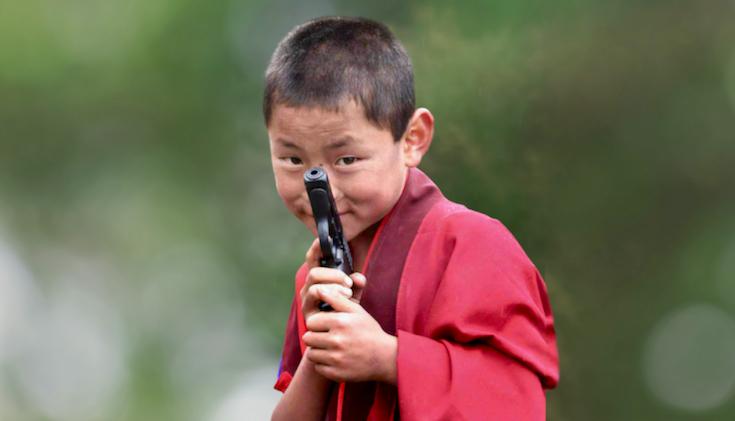 A boy monk holding a gun.