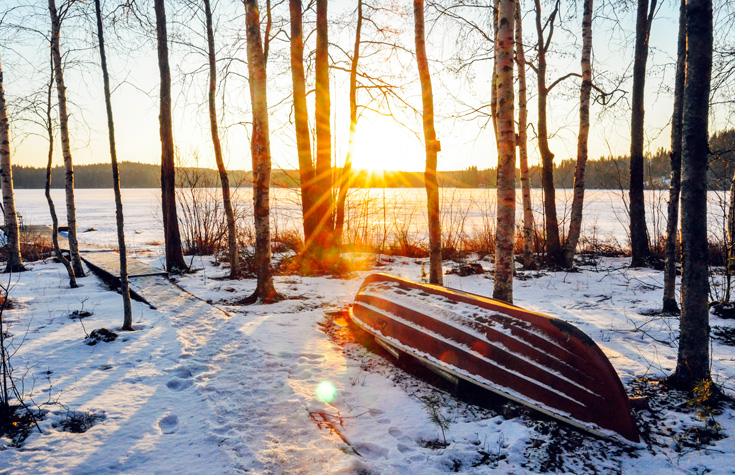Sun peeking through scattered trees. There is a bit of snow on the ground and a turned over canoe with a dusting of snow.