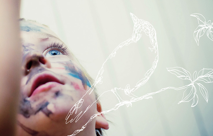 A child with paint on it's face. The child is looking up and has blue eyes. There is a white line drawing of a bird overlayed on the photo.