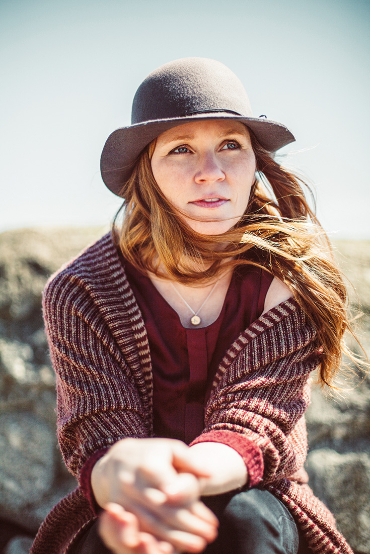 A woman wears a grey hat. She has red hair and is wearing a red tank under a red striped sweater.
