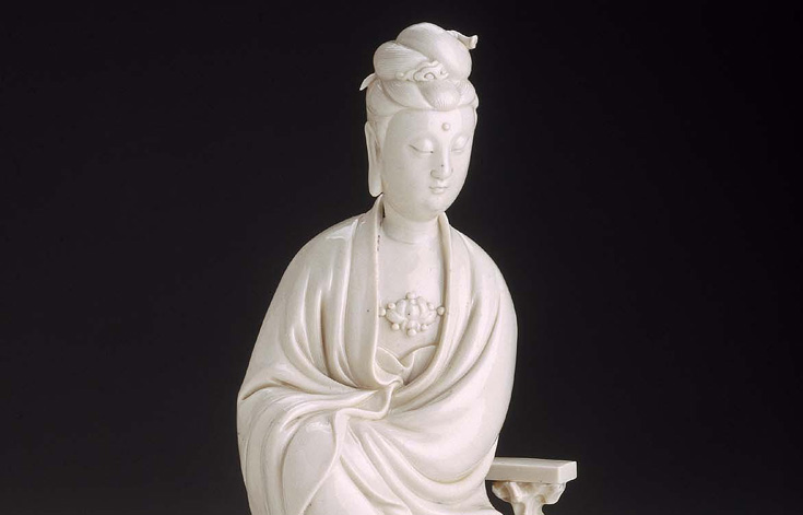 Statue of Guanyin, the Bodhisattava of Compassion. Marble statue against black background.