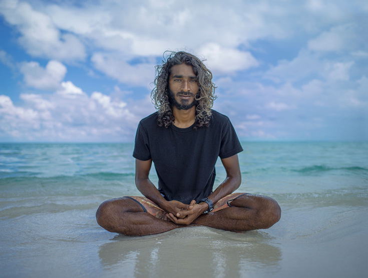 A photo of a man sitting on the beach, near the ocean. He is wearing a black t shirt and has long hair.