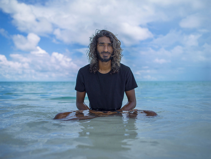 A photo of a man sitting waist deep in the ocean. He is wearing a black t shirt and has long hair.