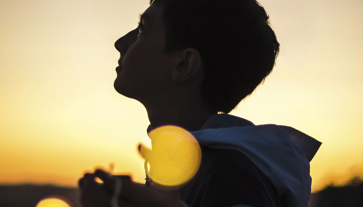 A young person at sunset looking towards the sky.