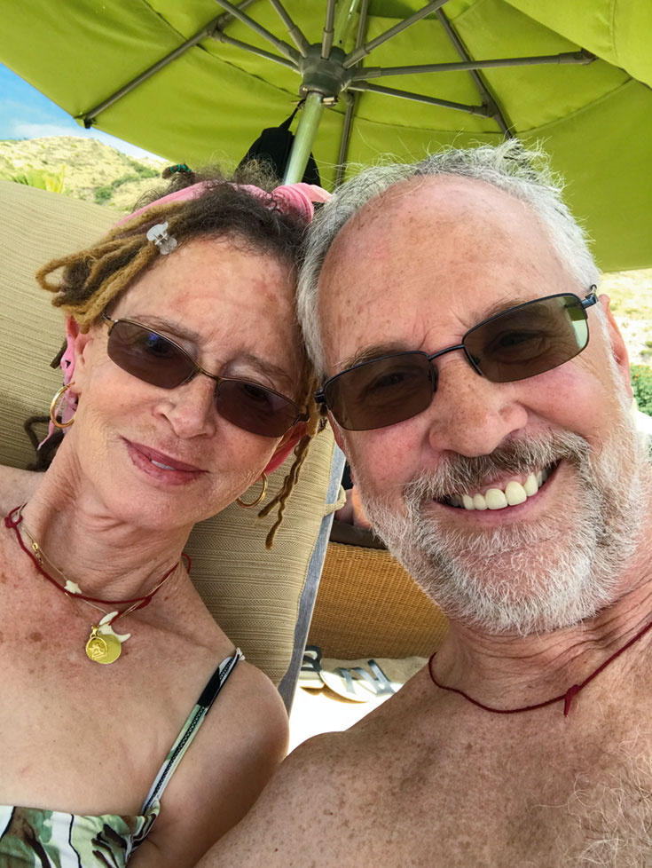 A couple on a beach. There is a green umbrella blocking the sun.