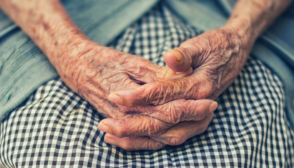 Hands of an elderly person, clasped together.