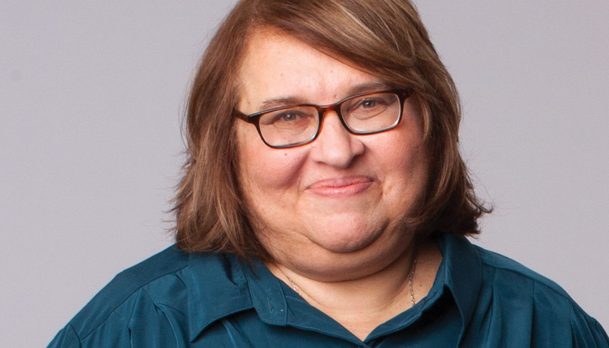 Sharon Salzberg. She is smiling and wearing a teal button up shirt.
