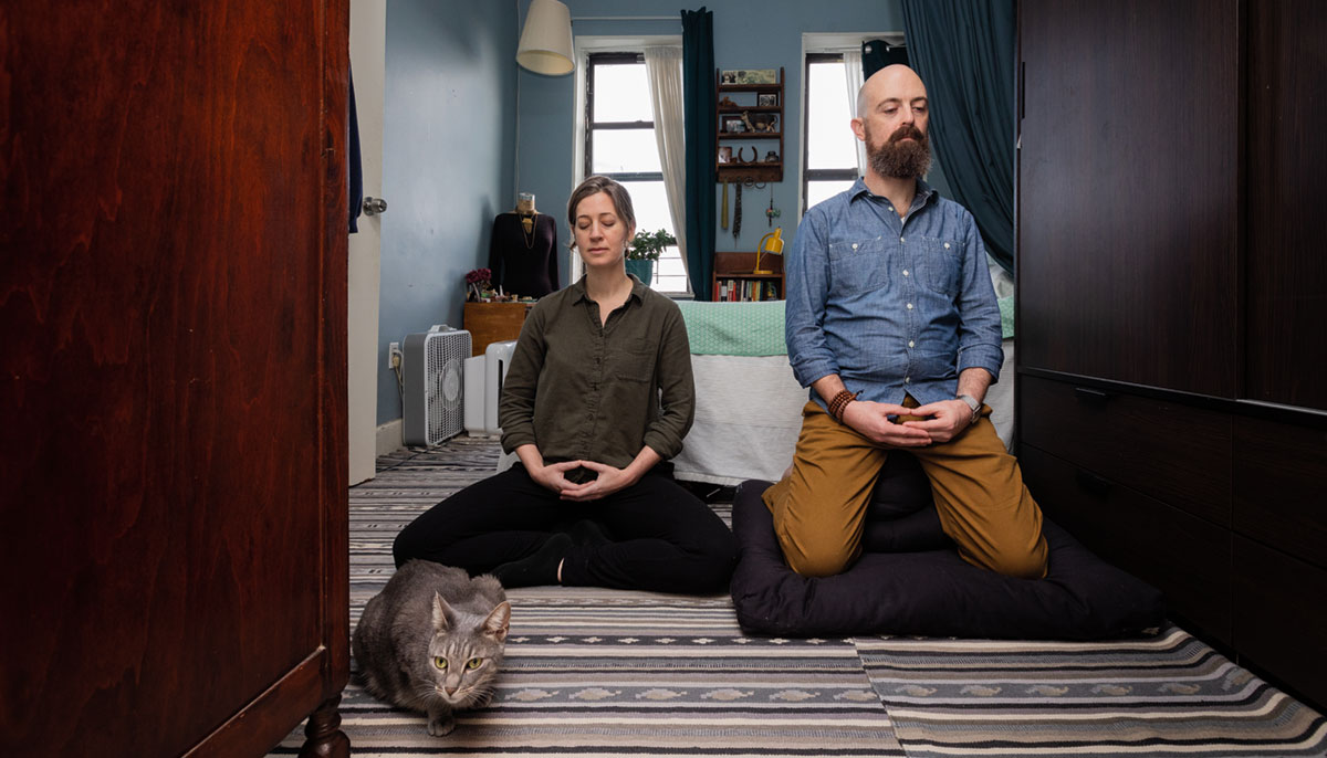 A couple meditating next to a cat. They are in a bedroom and sitting on a striped rug.