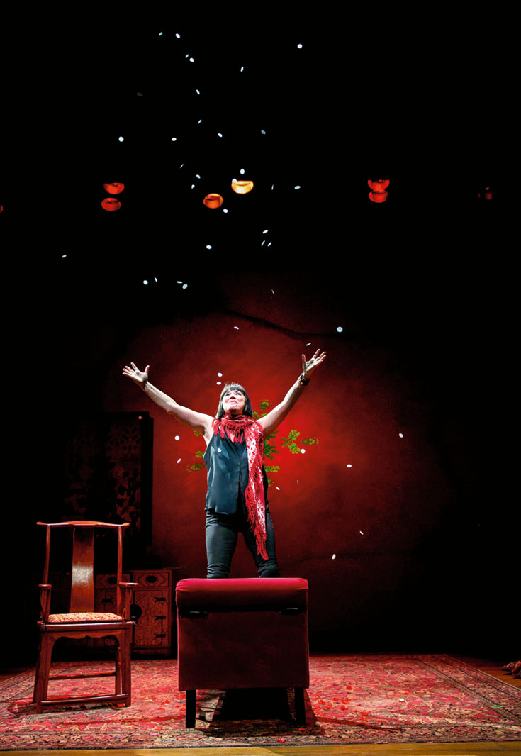 A woman on a stage. There is red lighting and the woman has her arms stretched towards the sky.