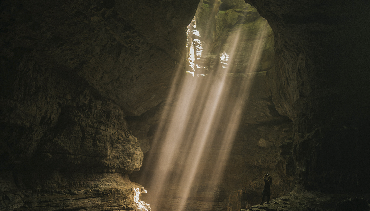 A photo from inside the cave with light peeking through a hole in the cave.