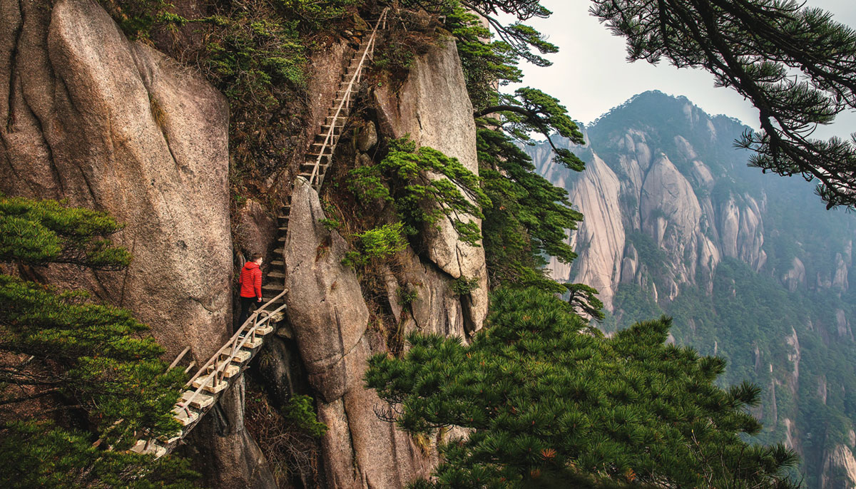 A man walking up wooden steps on the side of a cliff.