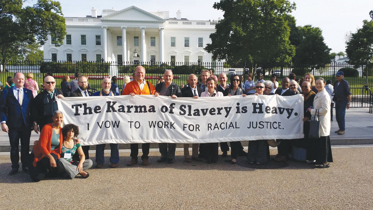 """A group of people standing outside the white house with a sign that reads """"the karma of slavery is heavy. I vow to work for racial justice."""""""