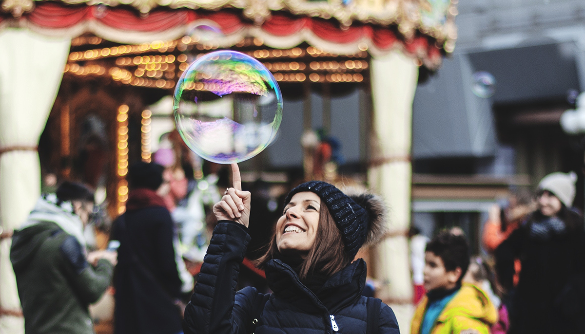 A woman in winter clothes pokes a big bubble in the air.