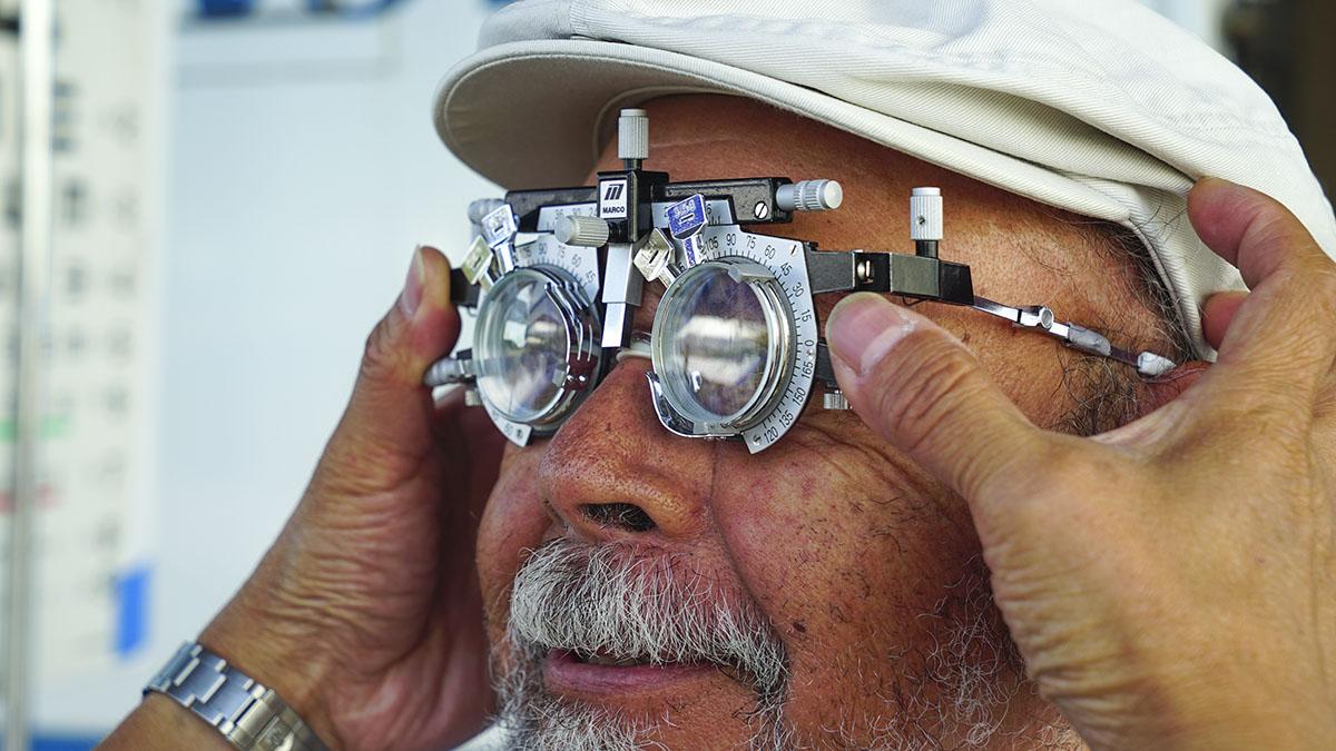 An older man wearing a hat having an eye exam.