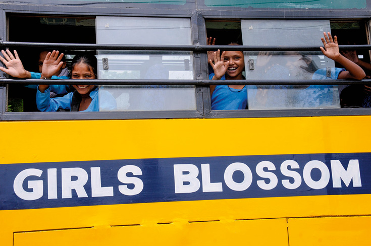 """Young girls waving out of a bus that reads """"girls blossom"""""""
