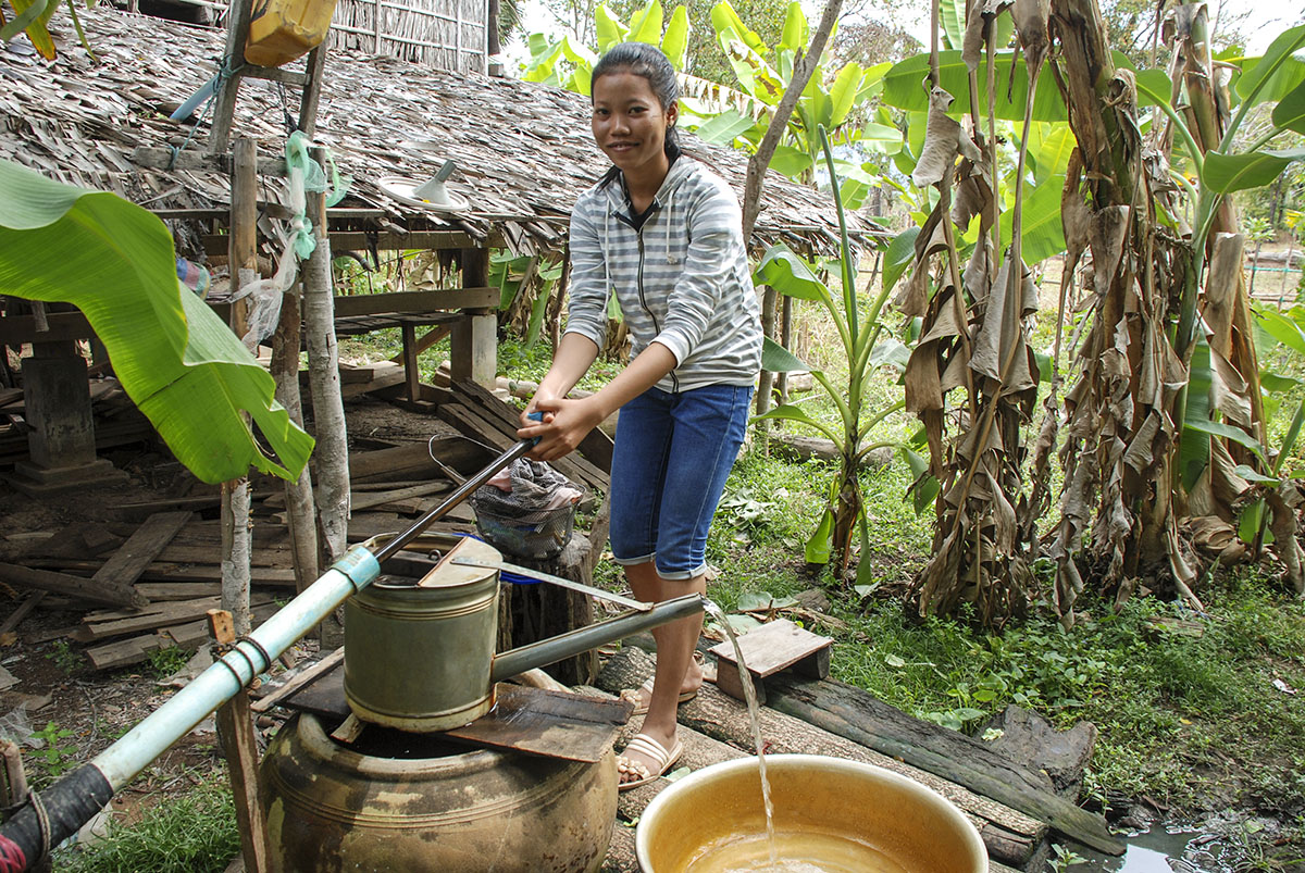 A woman wearing a striped hoodie and long jean shorts holds a water pump. There are lots of plants behind her.