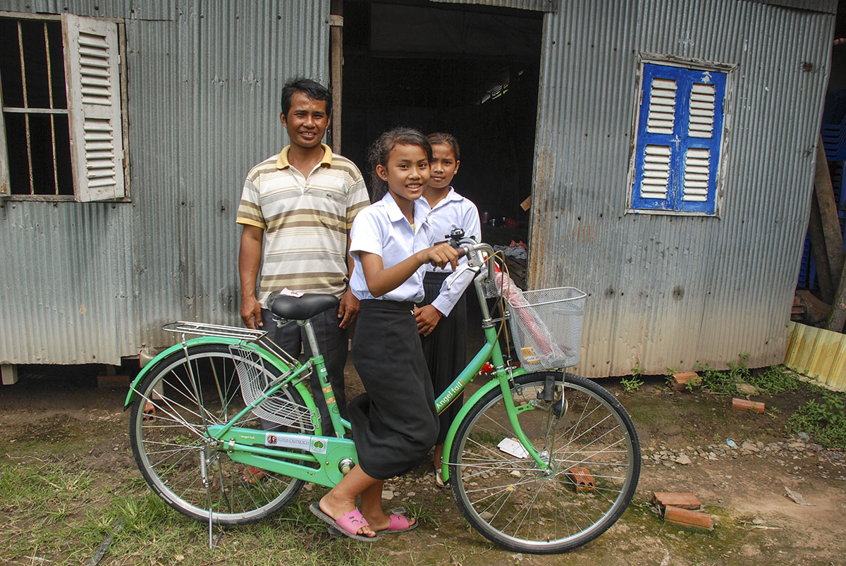 A young girl on a green bicycle. There is an older man standing behind her next to a young girl.