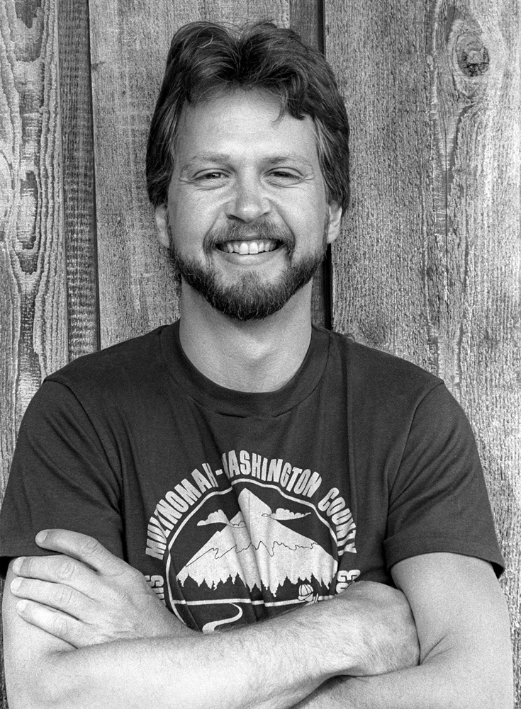 A black and white photo of a man wearing a tshirt. He is smiling with arms crossed against a wooden wall.