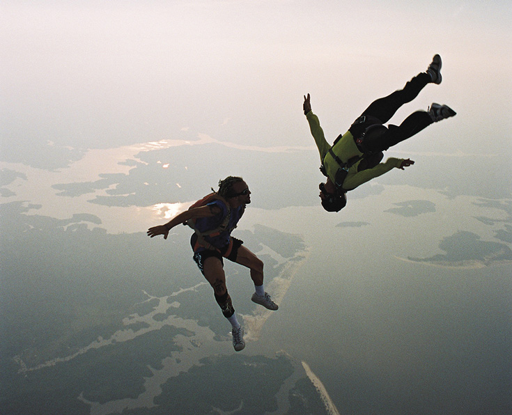 Two people skydiving. One is in the air upside down.