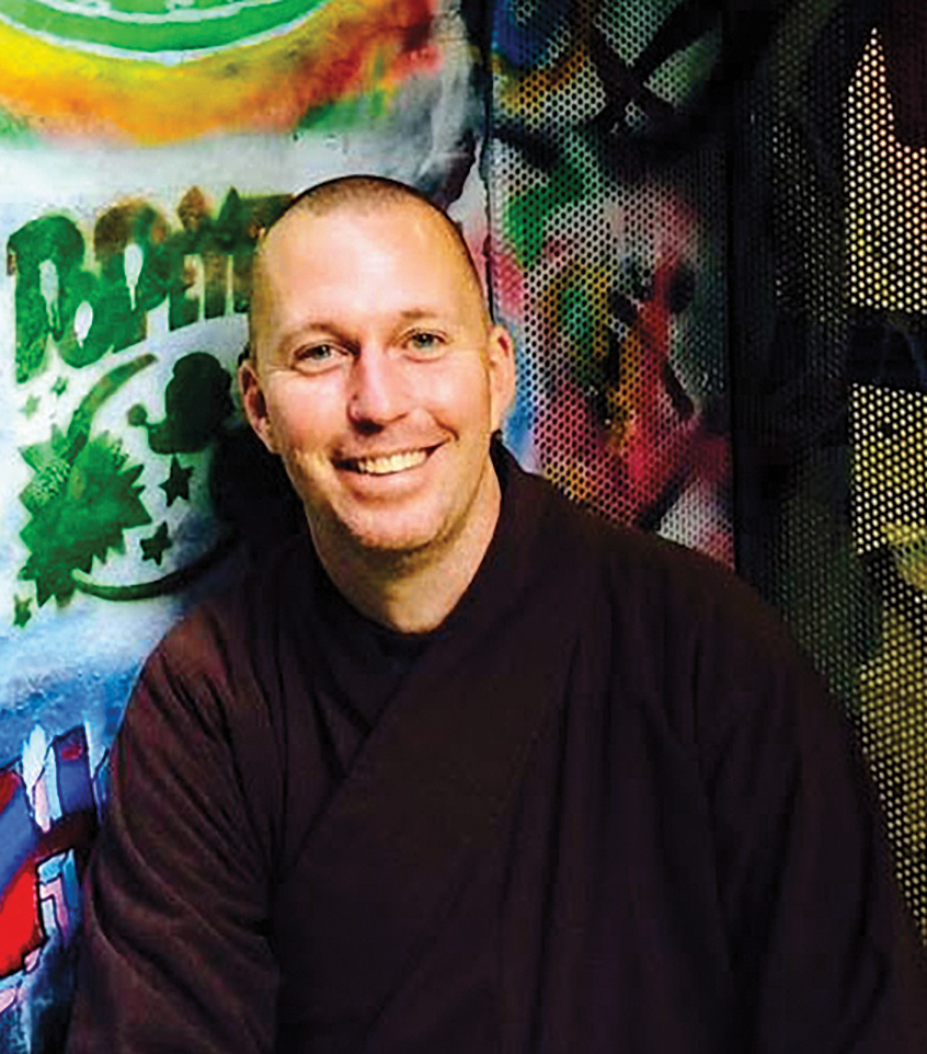 A man smiles in purple robes. There is a spray painted wall in the background.