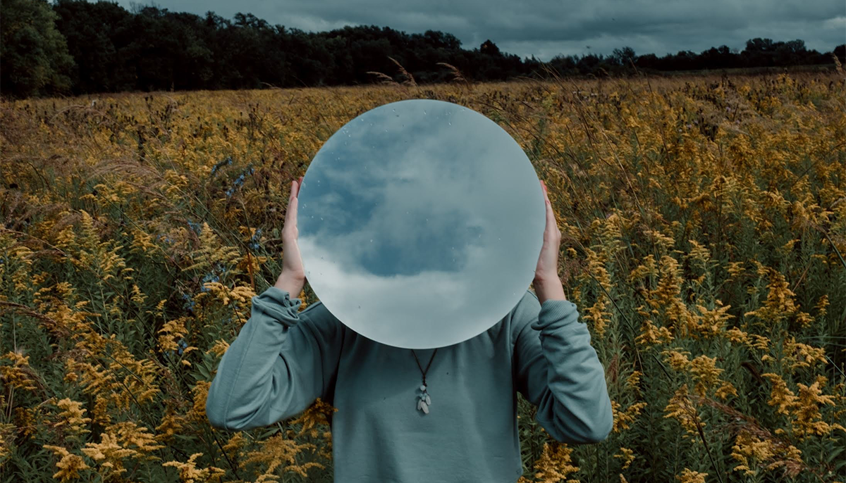 A photo of a woman in a field. She has a blue shirt and a necklace on. She is holding a round mirror which is reflecting a cloudy sky. It covers her face.