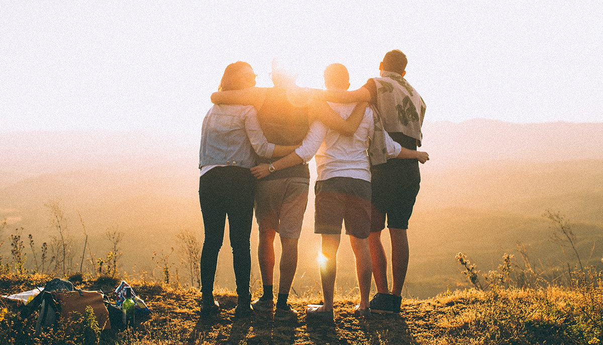 A photo of four people with their arms around each other looking off of a cliff. The photo is taken from behind.