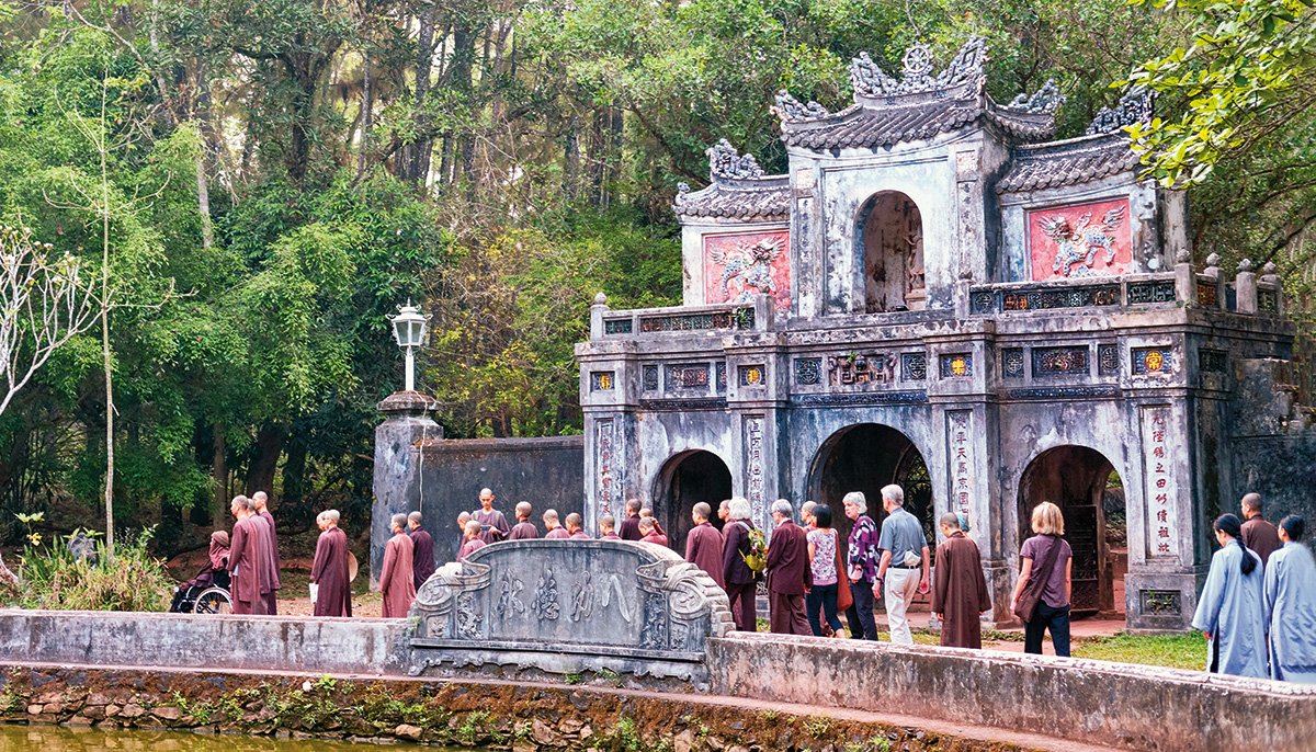 An old fashioned temple. There is a crowd of people in front of it, all wearing maroon robes.