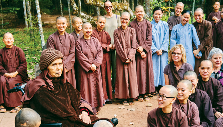A group of people in purple robes. There are two people with blue robes on the right side. Everyone is smiling.