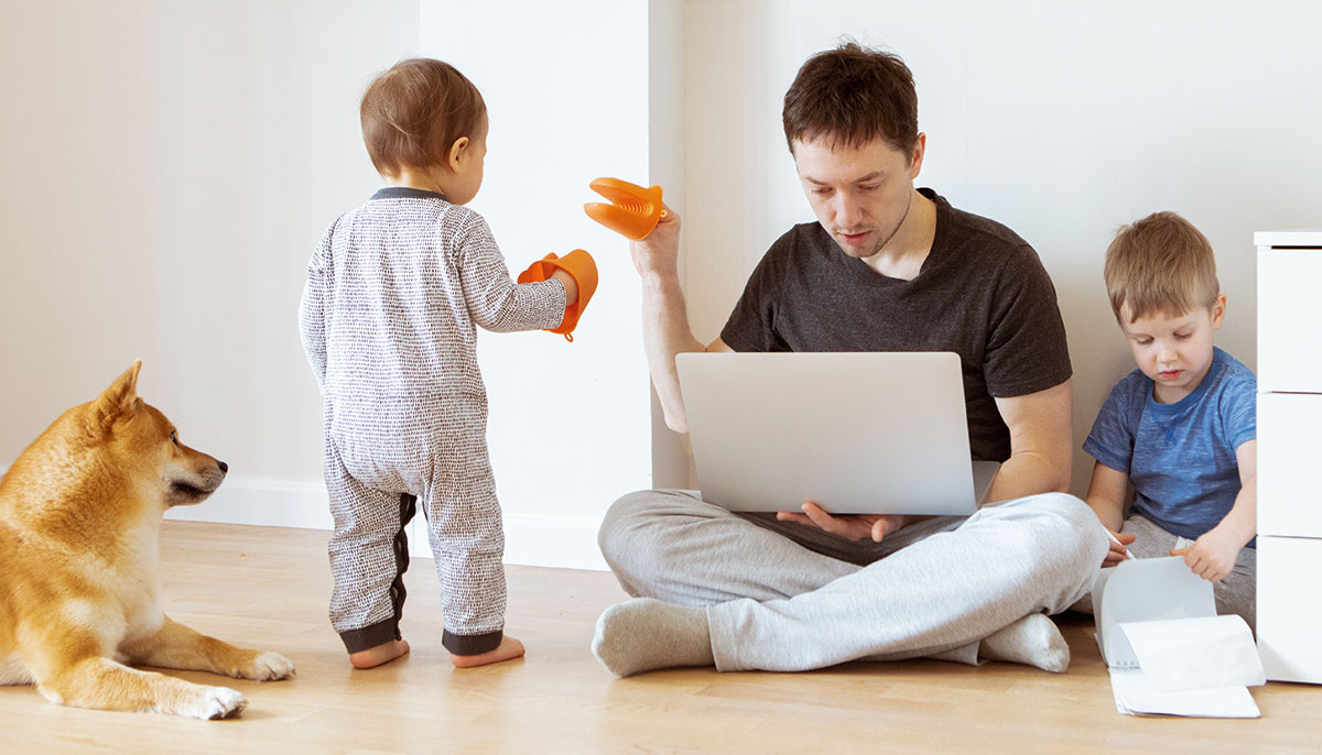 Photo of man attempting to work on computer while also taking care of two children and dog.