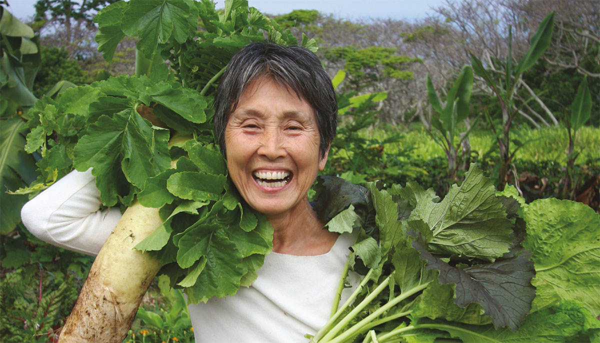 Mayumi Oda smiling in her garden holding up vegetables.