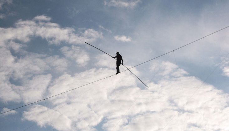 Image of person walking on a tightrope