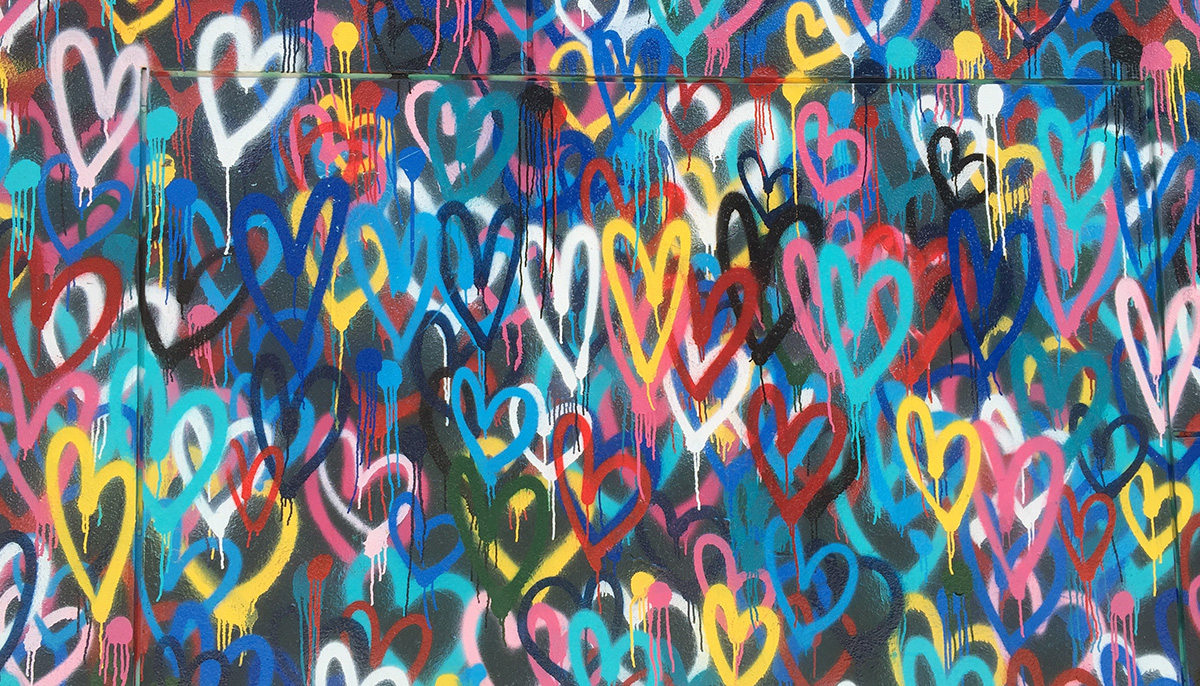 Wall covered in spray painted hearts.