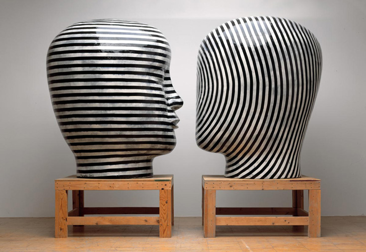 Two black and white heads on wooden platforms.