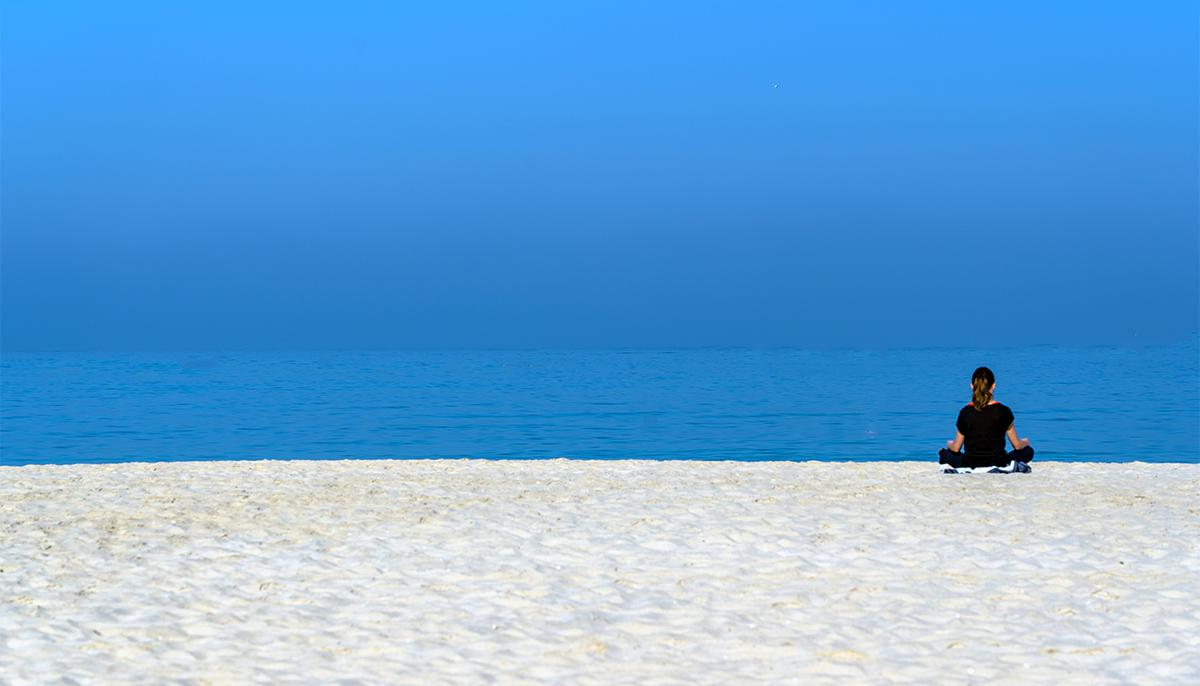 Woman meditating on beach.