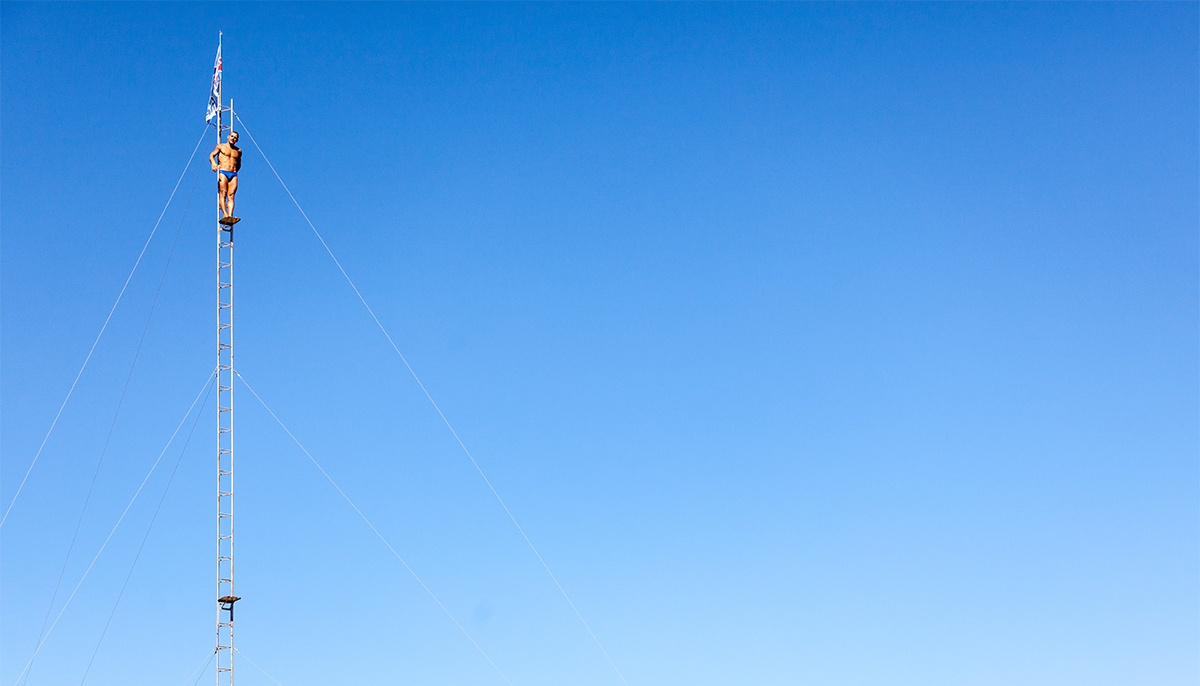 A person stands on a diving board. Only the blue sky is visible in the background and the photo is taken from far away.