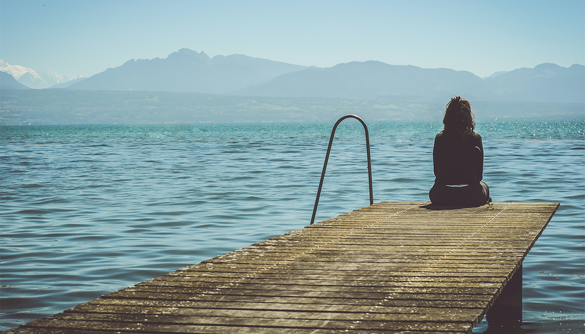 A woman sitting on the edge of a dock. She is looking over the ocean.