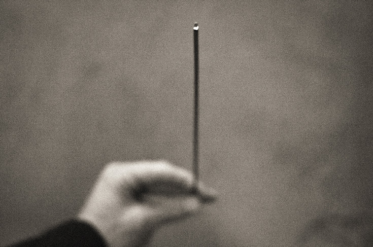 A blurry black and white photo of a hand holding an incense stick.