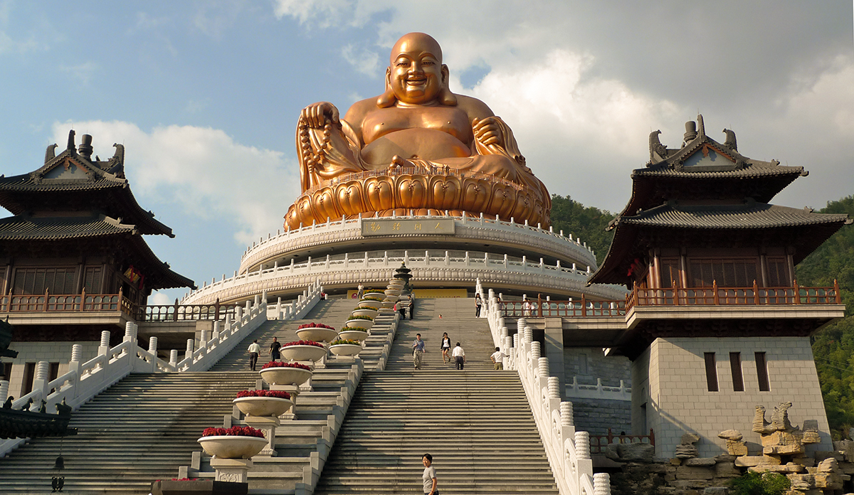 Jiuhua Shan in China. A golden statue at the top of a large staircase.