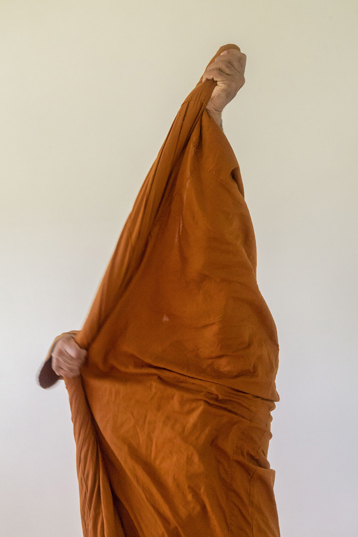 Person putting on orange robes. Only the orange and two hands are visible.