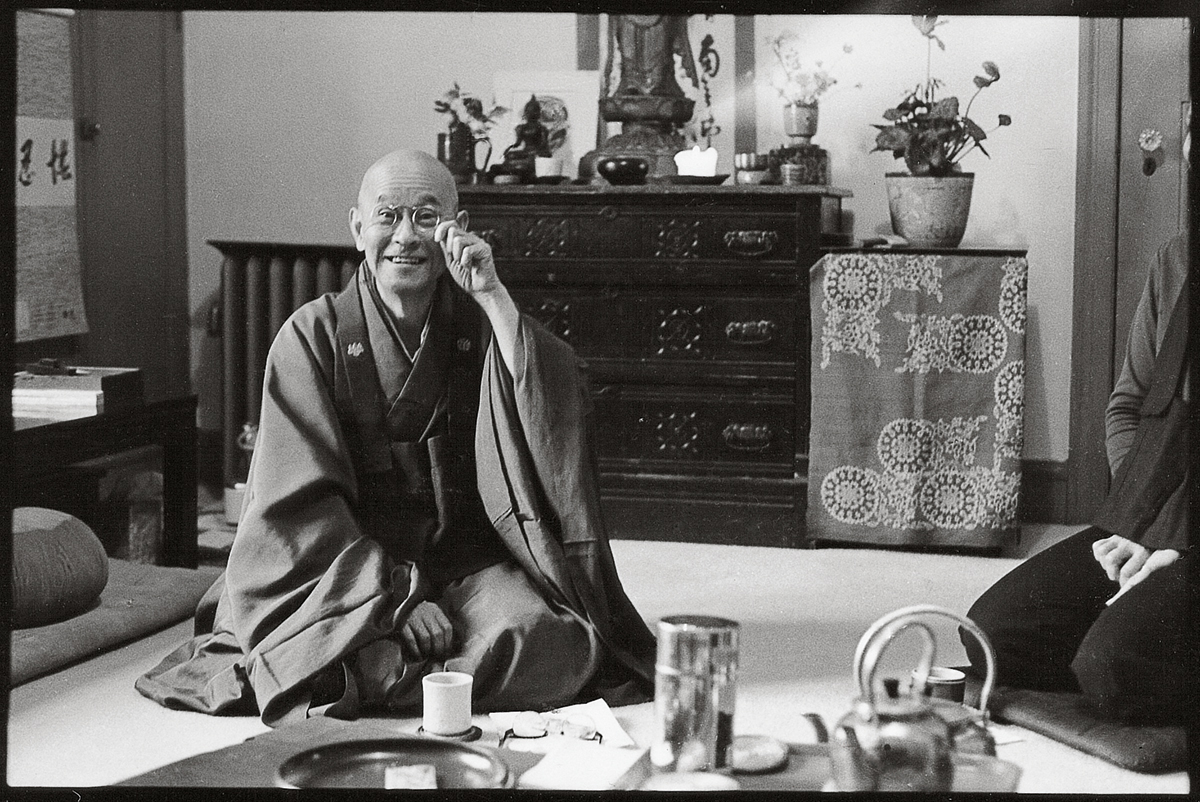 A person sitting on the ground in robes. They are fixing their circle shaped glasses on their face.