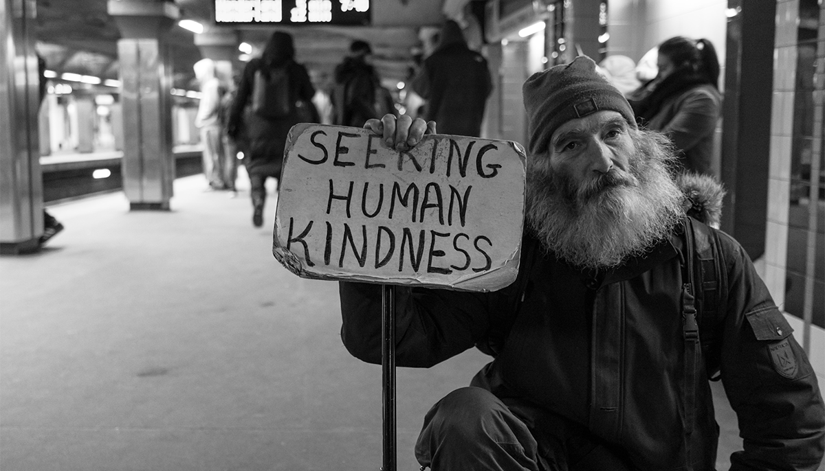 """Man in subway station holding up sign that says """"Seeking human kindness"""""""
