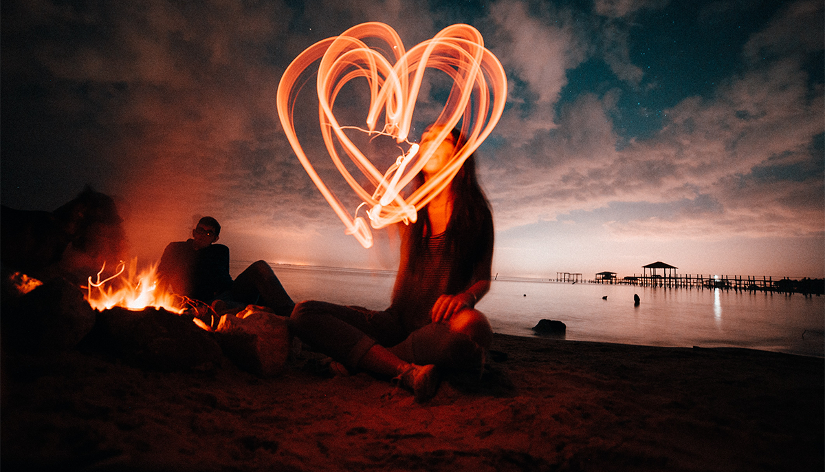Photo of woman sitting on beach making heart shape with sparkler
