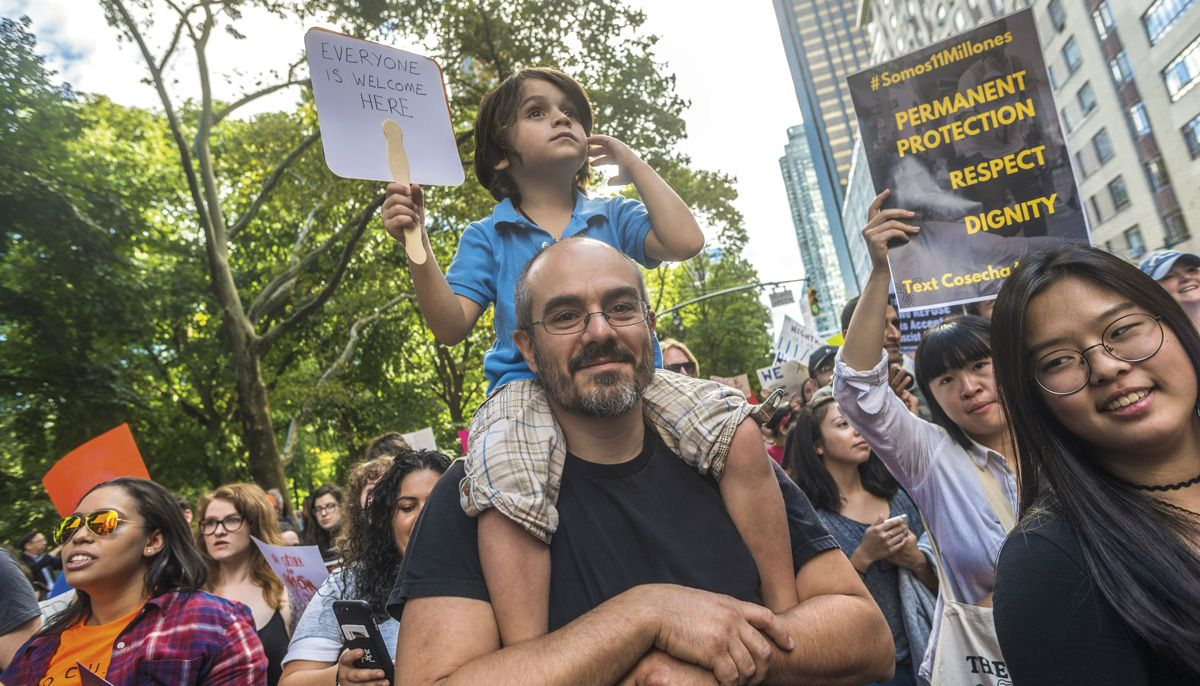 """A man with a young child sitting on his shoulders with a sign that reads """"everyone is welcome here."""" They are in a crowded protest."""